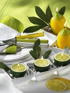 Kerzen in Form von ZitronenDekosteinekleine GefäßeLorbeerblätterIn kleine, mit Dekosteinen gefüllte Gefäße Kerzen in Form von Früchten