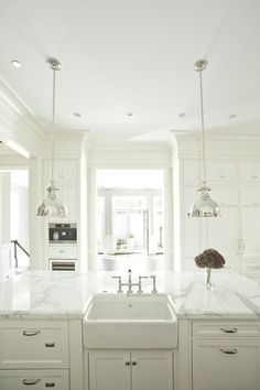 Small island sink in an all white kitchen.