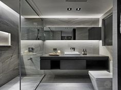Floating toilet and vanity with two sinks and a walk in shower (with two shower heads and a floating bench).