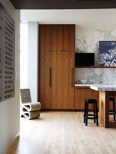 Simple materials, like a refrigerator, disguised with walnut, push the owner's art collection to the forefront; Frank Gehry cardboard Wiggle...