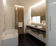 A minimal stílusú fürdőszoba tisztaságot sugárzó világos színeit kávébarna festésmintákkal bolondították meg, amelyek még meghatározóbbá válnak az álmennyezet széléről kitekintő melegfehér LED fénysornak köszönhetően.