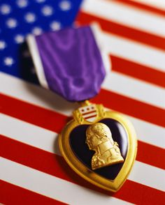 Purple Heart medal laying on the American Flag. Thank you for your service and your sacrifices for our country.