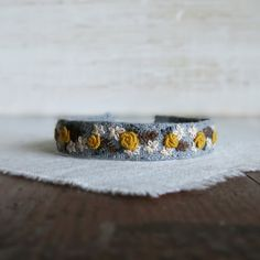 Floral hand embroidered cuff bracelet by Sidereal - Mustard yellow, cream and grey floral design.