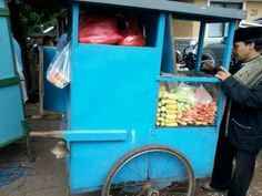 This is a picture of fruit cart which is selling fruit. This picture was taken on he 10th October 2013. It also has a man buying fruits form the fruit stall which is interesting