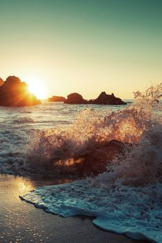 Sunlight reflects on waves crashing into the sand.