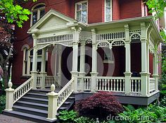 Century home with an ornate, wrap-around front porch.