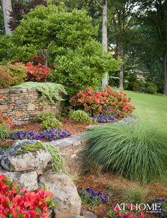Garden beds full of azaleas, petunias and lush miscanthus grass terrace down the hillside.