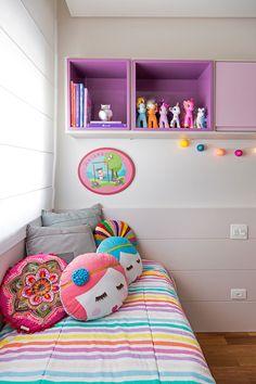 Decoração de apartamento colorido, no quarto infantil, quarto de menina, nicho roxo e branco, pôneis e almofadas estampadas.