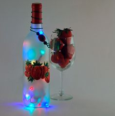 Strawberries hand painted onto a frosted wine bottle light filled with multicolored lights