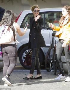 Happy days: Wearing skin-tight leggings and a chic coat, Olivia took the time to snap photos with fans