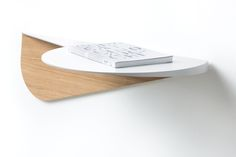 Slender curved sheet steel shelf with multi-layered wooden support panel. The rounded design resembles the shape of a tray, suggesting it can be used both for serving and standing things on. Design by Elena Salmistraro 2017