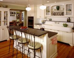 Cooktop stove in kitchen island.  Two-tiered kitchen island.  Farmhouse sink.