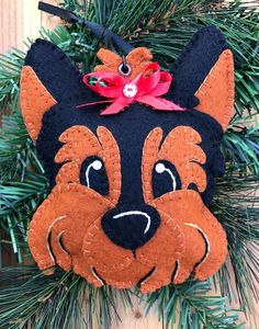 Wool blend felt Yorkie dog head ornament/hanger. Colors are black and copper. Ornament has been blanket stitched by hand in coordinating colors. Embroidered accents and brad eye accents. Hanging ribbon through eyelet and jump ring. Filled with soft polyfill. Ornament measures approximately 6 high X 4.5 wide. ** Follow us on Facebook for giveaways and sales info: https://www.facebook.com/FHGoldDesigns ** Follow us on Twitter for updates: @F_H_Gold ** Follow us on Pintere...