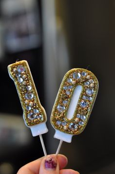 Take tacky number candles from the dollar store and glammed them up with gold glitter puff paint, rhinestones and beads.