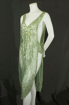 Sequined flapper green overdress, c.1925. The overdress is fashioned from sturdy cotton tulle and embellished with iridescent sequins. Garments that are mostly sequined are feather weight and easy to wear. The edges of the tunic are outlined with clear crystal beads. Antique beads do not have the rough edges found on modern beads; antique sequins exude a mellow glow. Front sideway