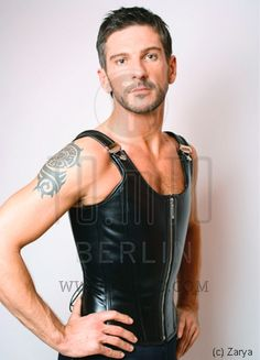 Men's overbust corset Mistral with shoulder straps is inspired by a classical vest, made of black leather with silver zipper and silver clasps.