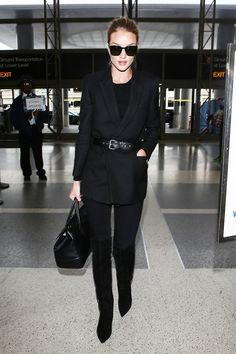 Rosie Huntington-Whiteley wears a black t-shirt, belted blazer, skinny jeans, thigh-high suede boots, a satchel, and square sunglasses