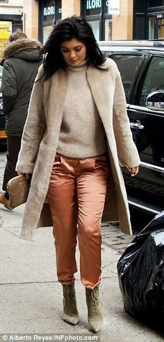 Dress up day: Kylie matched her soft coat with coppery trousers and a beige turtleneck swe...