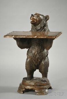 Black Forest Bear-form Occasional Table, 19th/20th century, carved as a bear standing on its hind legs and holding a rectangular tray, on shaped base with four feet.