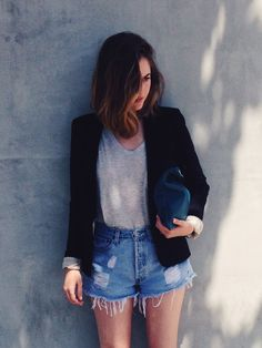 Black jacket with blue high waisted jean shorts. And a white blouse