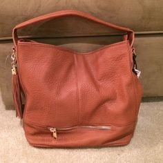"""Brown Tassel Purse Large brown faux leather purse with side tassel. Comes with detachable crossbody strap. Measures: 14""""H x 13""""W with a 9"""" strap drop. Purse is in good used condition, no stains anywhere. Only imperfection is on the side of handle where material is peeling off maybe an inch (pic 4)Trades Like Dreams Bags"""