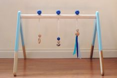 Small Life Studio's wooden baby play gym on Etsy - customizable wooden baby play gym gives parents loads of color combinations to consider for the legs and ball toppers, as well as the ribbon toy. And, unlike the two options above, this baby play gym comes with basic, developmentally appropriate hanging toys, making it a great new baby gift too. Made from natural hardwood and sealed in a safe beeswax, those hanging toys are designed to encourage reaching and grasping, as well