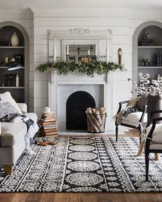 Cozy transitional fall-to-winter living room styling with fireplace mantel greenery, birchwood by the fire, and a black and white patterned area rug.
