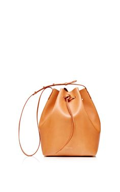c767fa71bfcf Shop Coated Leather Bucket Bag In Camello With Gold Interior. This bucket  bag from   Mansur Gavriel   features camello coated leather with gold  interior