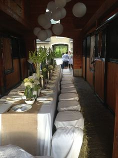 Noel Asmar , founder of Asmar Equestrian hosts a dinner in her barn - hay bales for seating, burlap table runner , wheat grass centrepieces with candles Horse looking in from the stalls