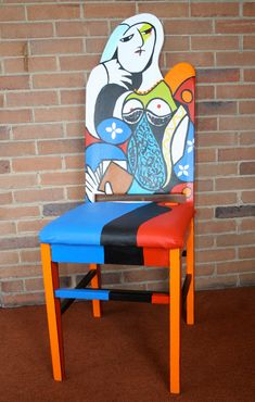 This upscaled painted chair pays tribute to Picasso' Seated Woman with Book cubist painting. The chair is painted in acrylic blends and shades of red,