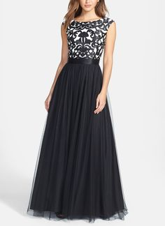 Laser-cut embroidery adds modern graphic styling to this timeless gown. A lustrous satin ribbon defines the cinched waist before the gossamer mesh skirt flares into a dramatic A-line silhouette.