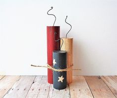 This trio of wood firecrackers measure 3 - 4 and 5 tall. Each one is cut, hand painted, stained, sealed, glued and tied together with twine and
