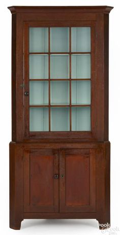 Winning bid:$2,200  Pennsylvania painted pine two-part corner cupboard, early 19th c., retaining an old dry red surface, 88 1/2'' h., 40'' w. - Price Estimate: $2000 - $4000