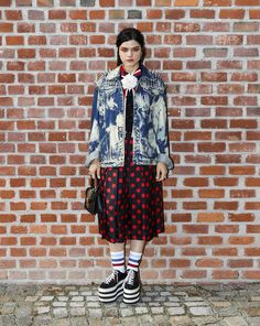 Soko attended the Gucci Fall Winter 2017 fashion show in an acid-washed, studded oversized jacket, silk pleated skirt, platform sneakers, Web socks and Gucci Sylvie mini bag.