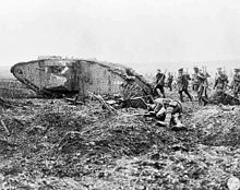 Files of Canadian soldiers with rifles slung follow close behind a tank:  there is a dead body in the foreground