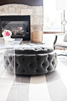 Chic living room boasts a round charcoal gray velvet tufted storage ottoman tucked under a clear acrylic waterfall coffee table, CB2 Peekaboo Clear Acrylic Coffee Table, placed atop a white and grays triped rug.