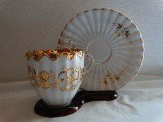 FANCY VINTAGE GOLD AND WHITE TEA CUP AND SAUCER RAISED DESIGN ON CUP