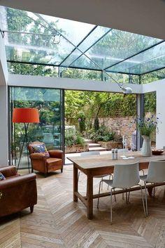 extension de maison avec toit en verre, parquet chevron, fauteuils Club, table à manger en bois massif et chaises design