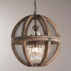 "Wire Sphere Crystal Chandelier - Small A charming crystal mini chandelier is nestled in a large solid wood sphere frame to create this unique country French chandelier. The distressed wood and wire combination bring the country French look together along with the bronze accents. A hinge on the sphere makes it easy to open for relamping. Hang over a large farm table or open foyer. 60 watt candelabra base bulb max. (18""Hx18""W)"