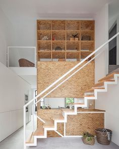 Crisp #white and warm brown define this modern #hallway. #Eycatcher are also the straight lines the team at Urbastudios opted for in the #stairs and the ceiling-high #shelf. Browse #homify for more #inspiration for your #interior!  #design #moderndesign #interiordesign #moderninterior #modernliving #modernhallway #entry #corridor #hall #stairwell #staircase #wood #timber #shelves #furniture #furnishing #decoration