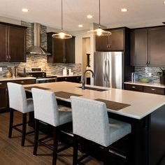 Athabasca showhome in Calgary, Alberta with an oversized island, chimney style range hood and oil-rubbed bronze faucet.