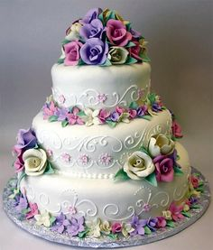 Vibrant three-tier cake with edible flowers. By Konditor Meister Elegant Wedding Cakes.