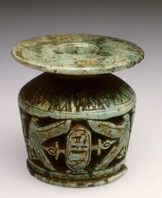 """Cosmetic Vessel of Meretnubt; Egypt, steatite with glaze, circa 1500 BC (New Kingdom) - This small cosmetic vessel is carved with an openwork frieze of heraldic birds flanking a cartouche with the name """"King's daughter, Nubet-meryt."""" Meretnubt was a daughter of King Thutmose I (1504-1492 BC). Separating the two heraldic groups are two snakes flanking a column. Above the openwork frieze is carved a series of alternating open and closed lotus flowers which ring the neck of the vessel."""