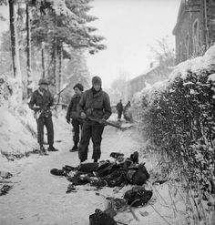 American soldiers looking at frozen corpses of German soldier killed during the Battle of the Bulge.