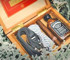 a box with a bow tie, suspenders, whiskey and a cigar is eveyrthing that a groomsman needs
