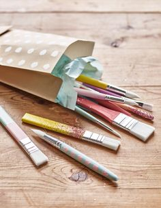 A bunch of hand-painted paint brushes lay in a gift bag.