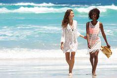Two girls walking on the beach wearing white beach dresses