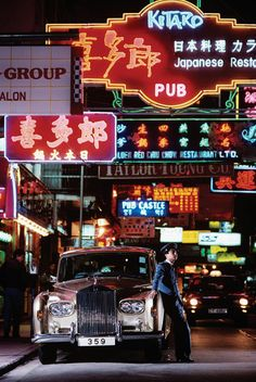 Tokio (Japan) nightlife. A Rolls Royce in a street with a lot of neon signs overhead.
