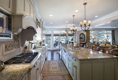 This enormous kitchen shares an open space with dining and living rooms, and features massive green island with marble countertop and bar style seating.