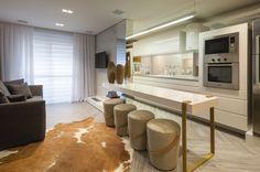 Um ambiente impactante com contraste de materiais, onde a marcenaria branca com brilho contrapõe-se ao piso desgastado. As arquitetas Letícia, Gisele e Klaudia otimizaram espaços com o auxílio da iluminação.
